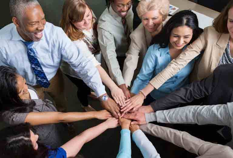 Diverse team of professionals with hands in teamwork huddle
